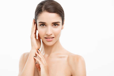 Beauty and Skin care concept - Close up Beautiful Young Woman touching her skin on white background. Foto de archivo