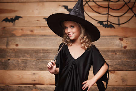 Halloween Witch concept - little witch child enjoy playing with magic wand. over bat and spider web background. Banque d'images