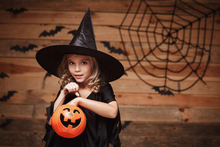 Halloween Witch concept - little caucasian witch child enjoy with halloween candy pumpkin jar. over bat and spider web background.
