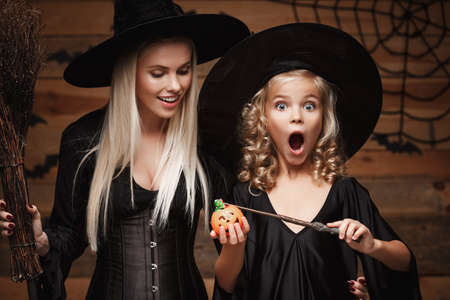 Halloween Concept - beautiful caucasian mother and her daughter in witch costumes enjoy using magic with magic wand to halloween pumpkin jar over bats and spider web on Wooden studio background.