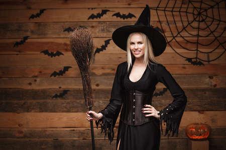 Concetto della strega di Halloween - tenuta sexy della strega di Halloween felice che posa sopra il vecchio fondo di legno dello studio.
