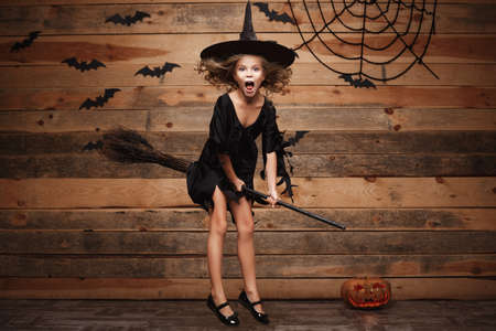 Halloween Witch concept - little caucasian witch child flying on magic broomstick over bat and spider web background.