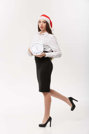 Rush time Concept - beautiful young caucasian woman running with clock isolated on white. Banco de Imagens