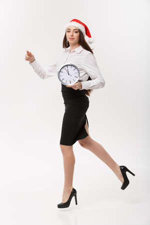 Rush time Concept - beautiful young caucasian woman running with clock isolated on white. Stock Photo