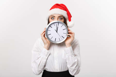 Time management concept - Young business woman with santa hat hiding behind a clock isolated over white background. Banco de Imagens