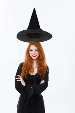 Halloween witch concept - Happy Halloween Sexy ginger hair Witch with magic hat flying over her head. Isolated on white background.