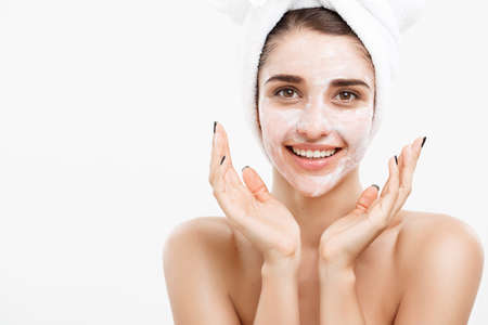 Beauty Skin Care Concept - Beautiful Caucasian Woman Face Portrait applying cream mask on her facial skin white background. Stock Photo