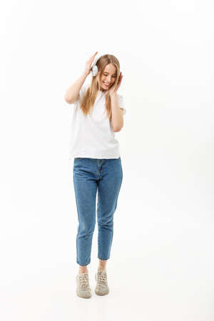 Lifestyle Concept: Portrait of a cheerful happy girl student listening to music with headphones while dancing isolated over white background Stock Photo