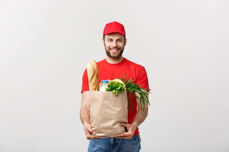 Concept de livraison - bel homme de livraison Cacasian transportant un sac d'emballage d'épicerie et de boissons du magasin. Isolé sur fond gris studio. Copiez l'espace.