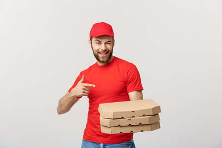 Delivery Concept: Handsome caucasian Pizza delivery man pointing finger. Isolated over grey background.
