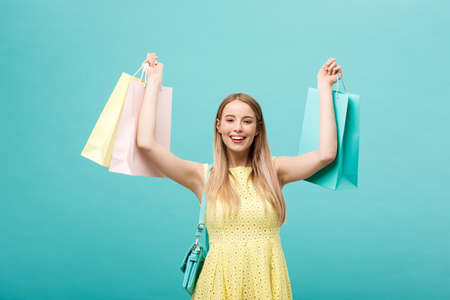 Lifestyle Concept: Portrait of shocked young attractive woman in yellow summer dressposing with shopping bags and looking at camera over blue background. Stock Photo