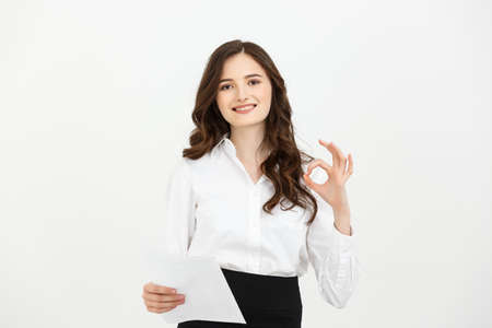 Portrait business woman showing OK hand sign smiling happy. Young pretty Caucasian businesswoman isolated on white background.