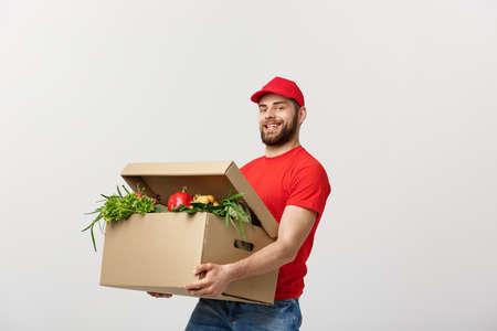 Concept de livraison - bel homme de livraison Cacasian transportant une boîte d'emballage de nourriture d'épicerie et de boisson du magasin. Isolé sur fond gris studio. Copiez l'espace. Banque d'images