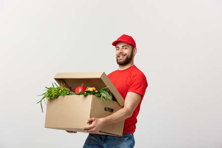 Delivery Concept - Handsome Cacasian delivery man carrying package box of grocery food and drink from store. Isolated on Grey studio Background. Copy Space.