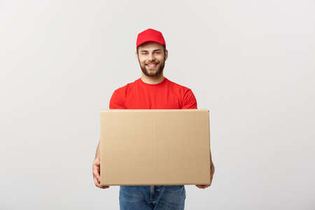 Young smiling logistic delivery man in red uniform holding the box on white background