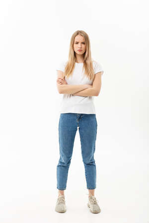 Full length portrait of a pretty young caucasian woman wearing jean and looking upset with her arms crossed