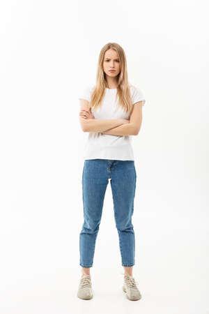 Retrato de cuerpo entero de una mujer caucásica bastante joven vistiendo jean y mirando molesto con los brazos cruzados Foto de archivo