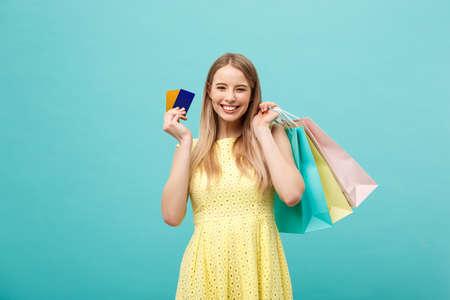 Concepto de compras y estilo de vida: hermosa joven con tarjeta de crédito y bolsas de colores. Aislado sobre fondo azul
