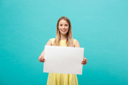 Lifestyle Concept: young beautiful girl smiling and holding a blank sheet of paper, dressed in yellow, isolated on pastel blue background Banco de Imagens
