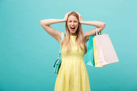 Shoping and Sale Concept: beautiful unhappy young woman in yellow elegant dress with shopping bag. Stock fotó
