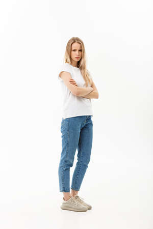 Serious confident young woman with long blond hair dressed in casual wear standing looking at the camera, full body over white