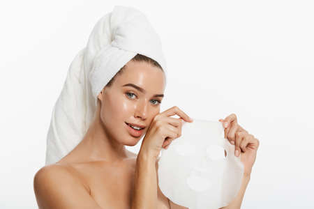 Beauty Skin Care Concept - Beautiful Caucasian Woman applying paper sheet mask on her face white background. Stockfoto