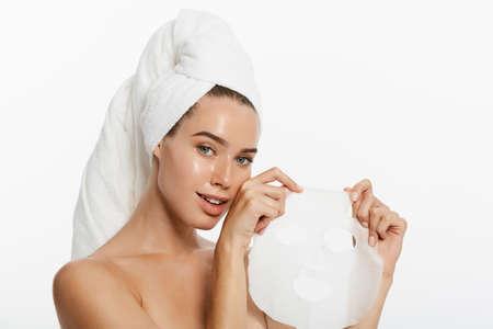 Schönheits-Hautpflege-Konzept - Schöne kaukasische Frau, die Papierblattmaske auf ihrem Gesichtweißhintergrund anwendet.