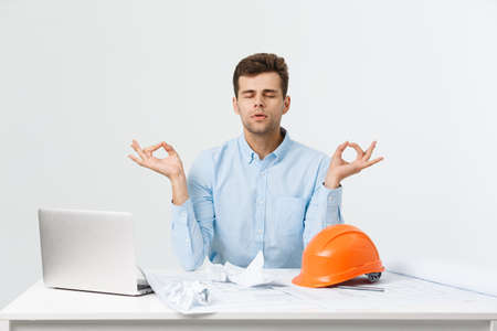 young handsome engineer or constructor man in blue suit practice yoga and relax at office room. Stock Photo
