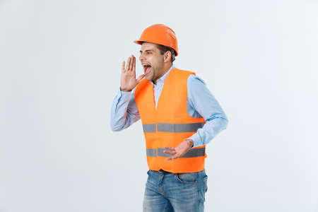 Angry engineer with angry face emotion shouting at someone raising his both hands, isolated on a white background. Stock Photo