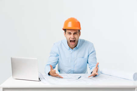 Young Engineer angry during working with laptop in office building site, he has problems with his new project manager