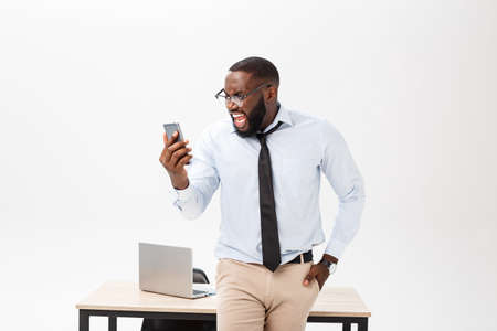 Irritated dark skinned young male enterpreneur being on working place feels very stressed and angry as cannot manage to do all work, surrounded with modern gadgets, looks in displeasure away Imagens