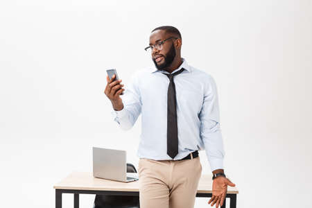 Irritated dark skinned young male enterpreneur being on working place feels very stressed and angry as cannot manage to do all work, surrounded with modern gadgets, looks in displeasure away Banco de Imagens
