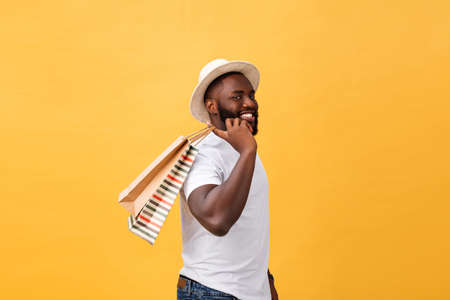 Happy african american man holding shopping bags on yellow background. Holidays concept