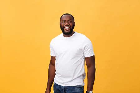 Porträt eines begeisterten afroamerikanischen Mannes mit positivem Lächeln, weißen perfekten Zähnen, schaut glücklich in die Kamera, ist erfolgreicher Unternehmer und trägt weißes T-Shirt.