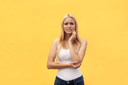 Beautiful young woman suffering from toothache on yellow background 版權商用圖片