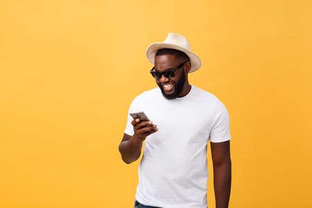 Alegre hombre afroamericano en camisa blanca mediante aplicación de teléfono móvil. feliz chico hipster de piel oscura leer noticias de la red social en el teléfono móvil. Foto de archivo