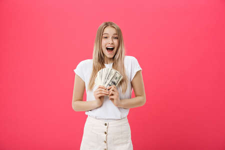 Young surprised shocked woman student with opened mouth holding bundle lots of dollars, cash money isolated on pink background. Education in high school university college