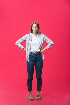 Thoughtful frowning young woman standing and thinking over pink background Foto de archivo