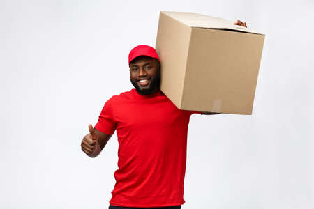 Delivery Concept - Handsome African American delivery man carrying package box. Isolated on Grey studio Background. Copy Space