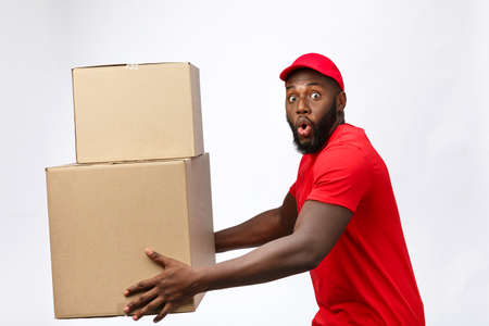 Delivery Concept - Side view Portrait of Happy African American delivery man in red cloth holding a box package. Isolated on Grey Background. Copy Space