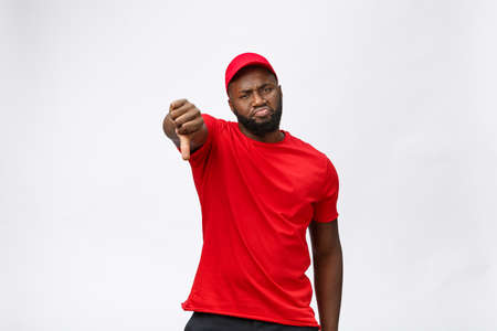 Delivery Concept - Portrait of Serious African American delivery man showing silly aggressive expression and unhappy. Isolated on Grey studio Background. Copy Space. Imagens - 114848720