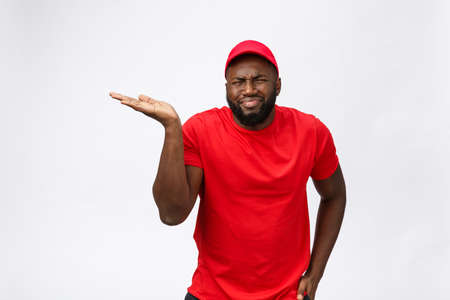 Delivery Concept - Portrait of Serious African American delivery man showing silly aggressive expression and unhappy. Isolated on Grey studio Background. Copy Space. Imagens - 114848726