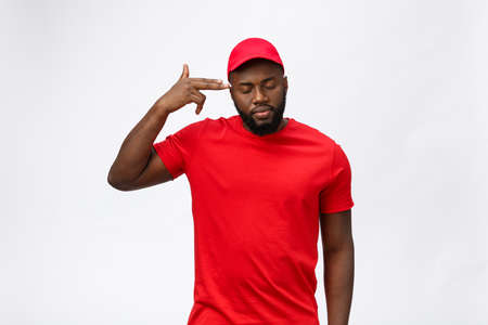 Delivery Concept - Portrait of Serious African American delivery man showing silly aggressive expression and unhappy. Isolated on Grey studio Background. Copy Space.