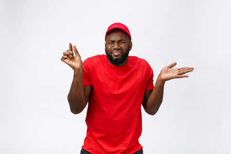 Delivery Concept - Portrait of Serious African American delivery man showing silly aggressive expression and unhappy. Isolated on Grey studio Background. Copy Space. Imagens - 114848735