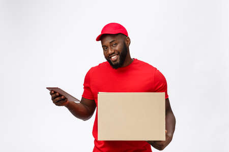 Delivery Concept - Portrait of Handsome African American delivery man or courier showing a confirmation document form to sign. Isolated on Grey studio Background. Copy Space 스톡 콘텐츠