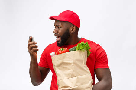 Delivery Concept: Handsome african pizza delivery man talking to mobile with shocking facial expression. Isolated over grey background. Imagens - 114852637