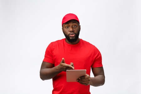 Delivery Concept - Portrait of Serious African American delivery man with tablet in silly aggressive expression and unhappy. Isolated on Grey studio Background. Copy Space.