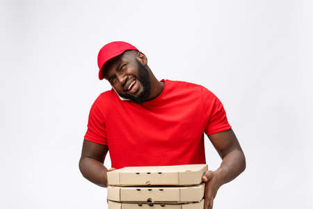 Delivery Concept: Handsome african pizza delivery man talking to mobile with shocking facial expression. Isolated over grey background.