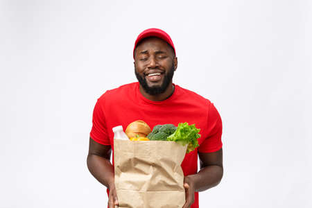 Young african american man holding grocery package in hands with shocking face. Isolated over Grey background. Foto de archivo