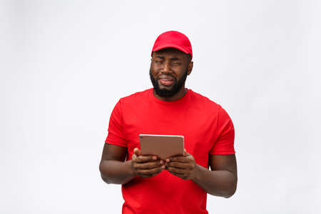 Delivery Concept - Portrait of Serious African American delivery man with tablet in silly aggressive expression and unhappy. Isolated on Grey studio Background. Copy Space. Imagens - 114852786